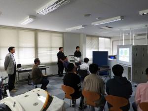 取材を受ける学内カンパニー 「アノナスライティング」と千葉寿技術専門職員の様子